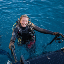 Jade coming out of the ocean with SCUBA gear on, She is smiling.
